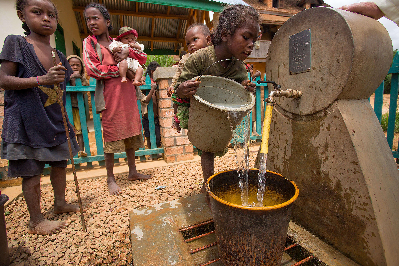 enfant versant eau dans seau borne fontaine